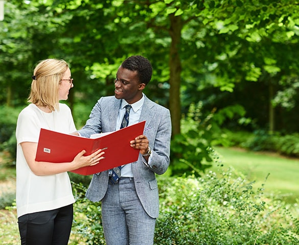 a young woman and man talking and holding a red file
