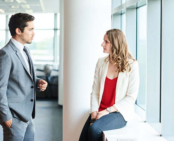 Man in grey suit and woman wearing red shirt talking
