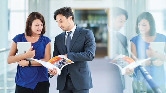Two people discussing a PwC brochure