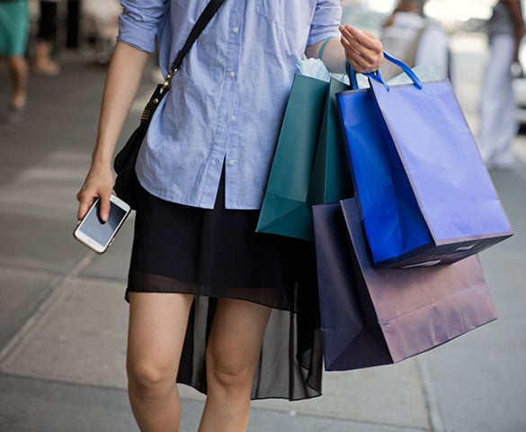 woman holding phone and multiple shopping bags